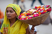 Indian Hindu woman selling ceremonial flowers and offerings during Festival of Shivaratri in holy city of Varanasi, India