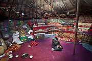 The interior of a yurt with a man drinking tea..Blankets filled with yak and sheep wool pile up against the inside wall of the yurt to insulate it from the constant winds. The floor carpet - bartered against 2 sheep - was acquired by Toorsoon in the lower valleys of Pakistan, a 10 days round trip leading over a 5000m pass. The wooden poles - over hundred years old - are handed over, generation after generation...