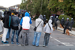 © Licensed to London News Pictures. FILE PICTURE DATED 07/08/2011. Enfield , UK . Youths and riot police with dogs face off opposite Enfield Town Railway Station . Following a night of riots and looting in Tottenham , looting spreads to other parts of London . Photo credit : Joel Goodman/LNP