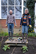 While planting new shrubs into fresh soil, a south London couple stand on a wooden pallet in the middle of their front garden during a weekend refurbishment of their home's plot, on 14th March 2021, in London, England.