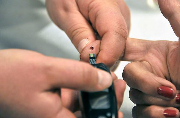 Nederland, Nijmegen, 22-1-2012Een vrouw laat haar bloedsuikerspiegel, cholesterolwaarde meten. Uit een druppel bloed wordt elektronisch de meting gedaan Foto: Flip Franssen