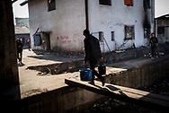 A migrant is seen carring whater in the Belgrade train station makeshift camp. About 900 refuggees get water for cooking and to wash themselfs from only two pipelines in the old train depot. March 17th, 2017, Belgrade, Serbia. Federico Scoppa