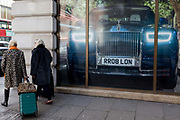 Two women, one wearing a Leopard  printed coat and pulling a bag behind her, walk past a large image of a Rolls-Royce, outside the car brands Mayfair show room, on 18th February 2020, in London, England.