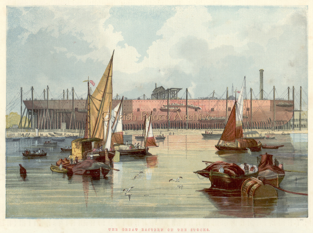 Great Eastern' on the stocks in John Scott Russell's (1808-1882) yard at Millwall on the Thames. Broadside view from the river. Double-hulled, of all iron construction, and powered by four steam engines driving both paddle wheels and screw propeller, she was intended for the passenger trade between Britain and Australia and India.  After a few troubled passenger voyages she was sold for £25,000, a fraction of the building cost of probably £500,000, and converted to a cable laying ship  In this role she was used in laying the Atlantic Telegraph Cable in 1865-1866, and other similar projects. She was Isambard Kingdom Brunel's (1806-1859) last great project.  He collapsed on her deck on her launch in 1858 and died a few days later.  From 'The Illustrated London News'. (London, 7 November 1857). Chromolithograph.