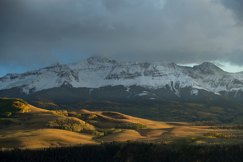 EVENING LIGHT ACROSS WILSON MESA, WITH FIRST SNOW ON SAN MIGUEL MOUNTAINS, SAN MIGUEL COUNTY, COLORADO