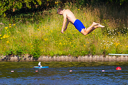 A man dives into the cool water at the men's swimming pond at Hampstead Heath in London. London, July 25 2019.