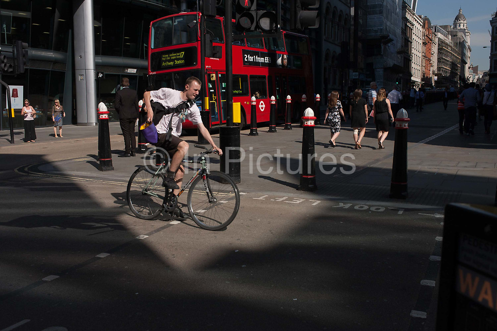 A cyclist pedals over Cannon Street and into a side street, on 24th August 2016, in the City of London, UK. He has just rounded the corner and reaches into a side pouch on this busy road running across the capitals financial district, founded by the Romans in the first Century.