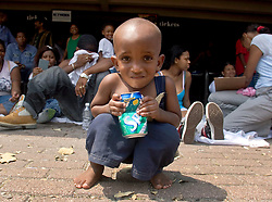 31st August, 2005. 'Hell on earth.' The Superdome in New Orleans, Louisiana where over 20,000 refugees from hurricane Katrina are crammed into hellish conditions. A wandering child squats in the hot sunshine outside the Superdome.