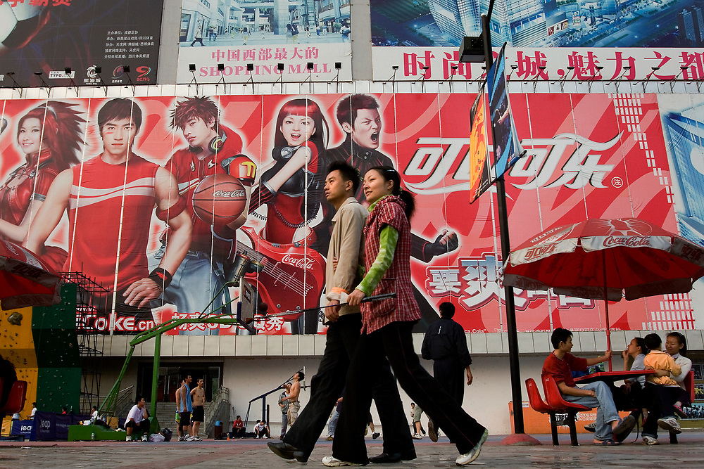 Locals gather to play basketball and hang out beneath an enormous Coca-Cola billboard featuring Chinese sports and pop stars outside the Panda Mall in Chengdu, Sichuan Province.