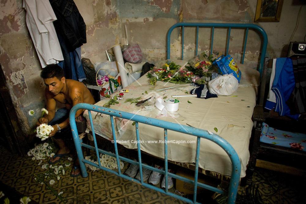 cuban man arranging flowers in bedroom