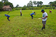 Men from the community work together to cut the grass of the football field with machetes - Communidad Siete de Augosto - Amazonas - Colombia