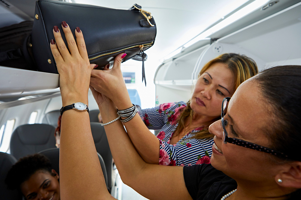 A Silver Airways flight attendant helps a passenger safely stow her carry-on luggage.  <br />