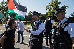A human rights activist remonstrates with a Metropolitan Police officer after being restrained when trying to stop a convoy of trucks delivering military equipment to ExCeL London for the DSEI 2021 arms fair on 8th September 2021 in London, United Kingdom. The third day of week-long Stop The Arms Fair protests outside the venue for one of the world's largest arms fairs was themed around demilitarising education.