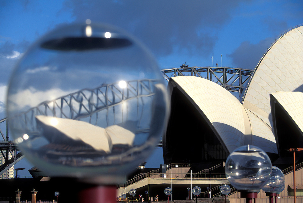 Australia, New South Wales, Sydney Opera House seen through street lamps by Royal Botanical Gardens and Sydney Harbour