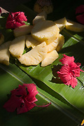 Slices of pineapple sitting on a palm leaf with red hibiscus flowers and illuminated by shafts of sunlight