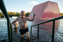 © Licensed to London News Pictures. 01/10/2018. London, UK. A swimmer leaves the Serpentine Lido in Hyde Park at sunrise this morning. Temperatures in the capital were cold this morning, but are set to reach over 20 degrees Celsius later this week, higher than average for the time of year. Photo credit : Tom Nicholson/LNP