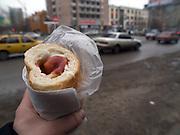 Strassenszene mit einem russischen Hot Dog aus der Mikrowelle serviert in einem Plastikbeutel im Zentrum der sibirischen Hauptstadt Nowosibirsk. Billboard der Metro Gruppe.<br /> <br /> Street scene with a Russian Hot Dog in the center of the Sibirian capital Novosibirsk.