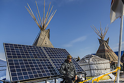 December 3, 2016 - Cannonball, North Dakota, United States - A veteran sits on one of the mobile solar panels. Veterans arrived en mass to Standing Rock, bringing a massive amount of supplies including winter clothing, food and firewood by the truck load.  Over 5000 veterans are anticipated to arrive by Sunday evening, prior to various actions slated to place. (Credit Image: © Michael Nigro/Pacific Press via ZUMA Wire)
