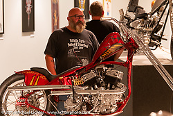 """Canadian Scotty Busch checking out Josh Sheehan's Buzzards Luck is custom Frisco-style chopper in the front and a race bike in the rear. Built with a customized 1936 VL Frame and a 1947n 45"""" Flathead bottom and 1953 K Model top end. On view in the What's the Skinny Exhibition (2019 iteration of the Motorcycles as Art annual series) at the Sturgis Buffalo Chip during the Sturgis Black Hills Motorcycle Rally. SD, USA. Thursday, August 8, 2019. Photography ©2019 Michael Lichter."""
