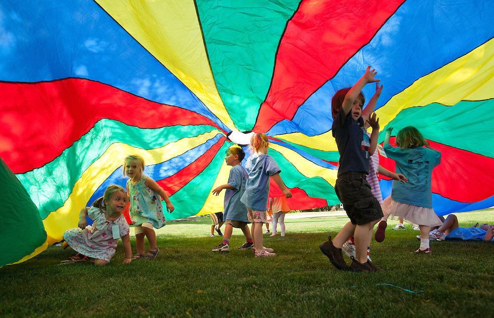 Cohasset, MA 07/13/2012<br /> Children in the Cohasset Recreation Summer program play with a parachute on the town common on Friday morning.
