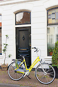 Yellow bicycle parked outside traditional town house in Amsterdam, Holland, The Netherlands