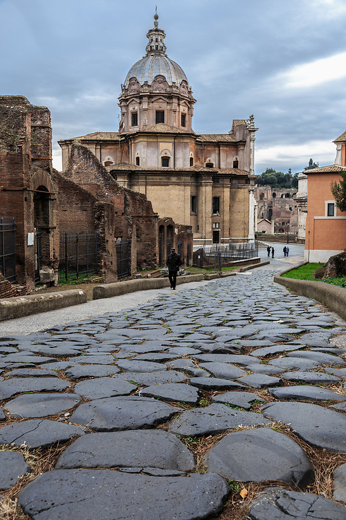 A cobbled street in Forum Romanum in Rome, Italy. For centuries the Forum was the teeming heart of ancient Rome. Here triumphal processions, elections, public speeches, criminal trials and commercial affairs happened.
