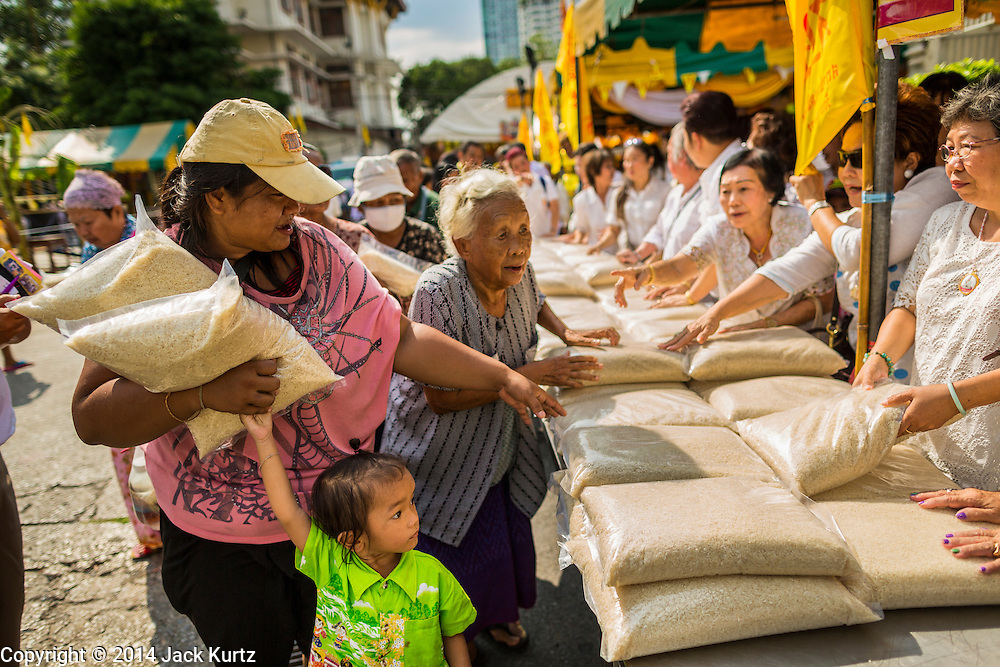 01 OCTOBER 2014 - BANGKOK, THAILAND: Indigent people pick up free rice at Wat Yannawa (also spelled Yan Nawa) during the Vegetarian Festival in Bangkok. The Vegetarian Festival is celebrated throughout Thailand. It is the Thai version of the The Nine Emperor Gods Festival, a nine-day Taoist celebration beginning on the eve of 9th lunar month of the Chinese calendar. During a period of nine days, those who are participating in the festival dress all in white and abstain from eating meat, poultry, seafood, and dairy products. Vendors and proprietors of restaurants indicate that vegetarian food is for sale by putting a yellow flag out with Thai characters for meatless written on it in red.     PHOTO BY JACK KURTZ