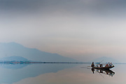 A fisherman on his boat on Dal Lake, Srinagar, Kashmir, India