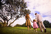 A couple walks their toddler daughter up a grassy hill.