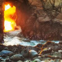 Winter sunset light through a sea arch on Pfeiffer Beach, Big Sur Coast, California.