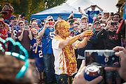 """SHOT 10/22/17 9:38:22 AM - The ketchup and mustard shower while tailgating at the Hammer's Lot at the Pinto Ron tailgate party before the Buffalo Bills faced the Tampa Bay Buccaneers in Orchard Park, N.Y. Ken Johnson, better known as """"Pinto Ron"""", (born 1958) is a Buffalo Bills fan known for attending every single Bills home and away game and hosting a tailgate party since 1994. He is known for his red Ford Pinto and antics cooking food on his car hood in a variety of objects such as a shovel and army helmet; furthermore, he holds a tradition of being doused in ketchup and mustard. Most notably he served shots out of a bowling ball until he was forced to shut down by the National Football League (NFL) Johnson moved his tailgate party to private property next to the stadium where the NFL has no jurisdiction and was able to resume serving bowling ball shots. He has been featured in multiple NFL Films, as well as the made-for-TV movie Second String. (Photo by Marc Piscotty / © 2017)"""