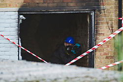 ©  London News Pictures. 15/10/2012. Harlow, UK. A fire investigation team photographing damage at the rear of a property  on Barn Mead, Harlow, Essex where three children and a woman have died and three others are in hospital following a house fire. Two boys aged 13 and six, a girl aged 11 and the woman were declared dead at the scene. A nine-year-old boy and a three-year-old girl have serious burns and a man has minor burns. Photo credit : Ben Cawthra/LNP