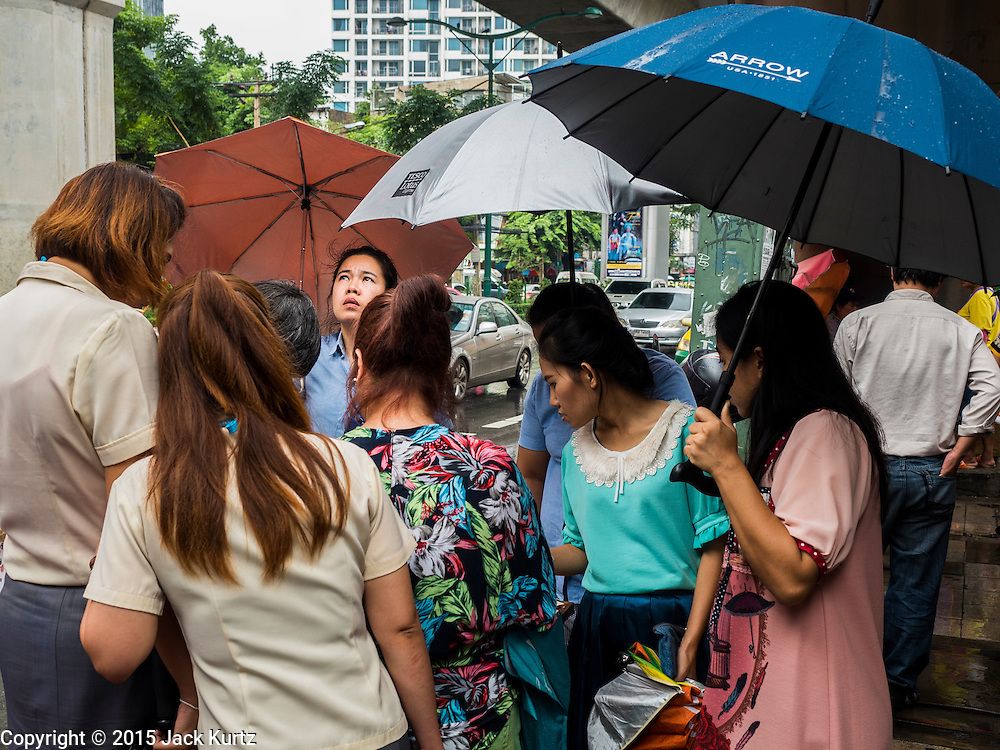 """16 SEPTEMBER 2015 - BANGKOK, THAILAND:  People under umbrellas buy lottery tickets in the rain in Bangkok. The remnants of tropical storm """"Vamco"""" hit Bangkok Wednesday. The storm, downgraded to a tropical depression, brought bands of rain to central Thailand, including Bangkok. The Thai Meteorological Department said the storm would help alleviate the drought that has gripped Thailand since late last year.    PHOTO BY JACK KURTZ"""