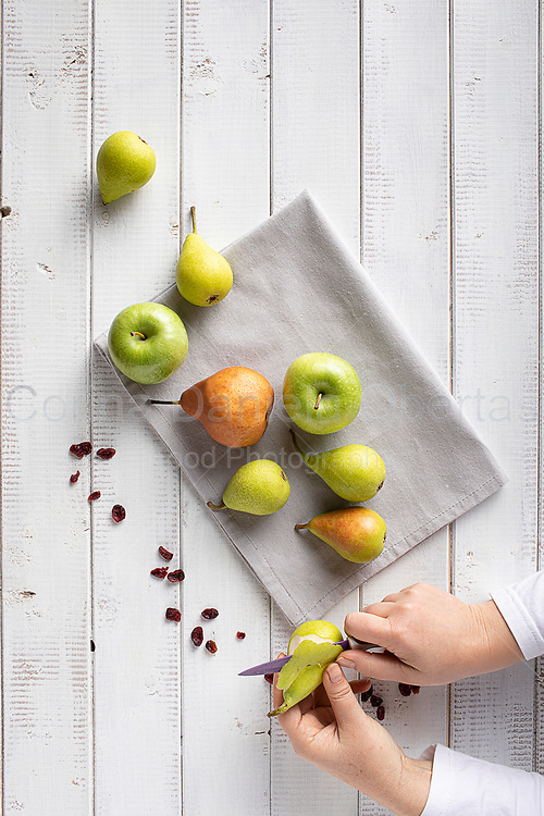 Hands of woman peels pears necessary for the preparation of pears in syrup