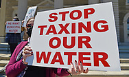 Mineola, New York, USA. April 26, 2021. Activist at rally holds sign saying: STOP TAXING OUR WATER. Faced with a 26% rate increase from New York American Water going into effect May 1, 2021, activists and residents who are NYAW customers rally to urge NYS Assemby to push through legislation, before that date, corresponding with NYS Senate Bill S989A to establish a Nassau County Water Authority and except water works corporations in counties of populations over one million from a special franchise tax.