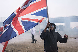 October 1, 2016 - Calais, France - A participant holds up the Union Jack during clashes with French anti-riot police during a march in support of migrants and refugees in the so-called 'Jungle' camp in the French northern port city of Calais on October 1, 2016. Between 7,000 and 10,000 migrants are currently living in the ''Jungle'', the launchpad for their attempts to stow away on lorries heading across the Channel to England. Rights groups have criticised the hardship and dangers facing the migrants living in the camp, particularly the hundreds of unaccompanied minors. (Credit Image: © Julien Mattia/NurPhoto via ZUMA Press)