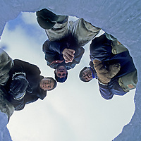 BAFFIN ISLAND, Nunavut, Canada. Inuit hunters surround fishing hole they are chopping in frozen lake in Stewart Valley.