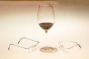 A glass of red wine and two pairs of glasses against a white background The Dolly Irigoyen - famous chef and TV presenter - private restaurant, Buenos Aires Argentina, South America Espacio Dolli