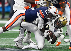 UCF Knights running back Adrian Killins Jr. (9) is tackled by Auburn Tigers linebacker Montavious Atkinson (48) during the Chick-fil-A Peach Bowl NCAA college football game January 1, 2018, in Atlanta. (David Tulis via Abell Images for Chick-fil-A Peach Bowl)