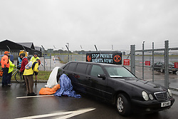 Farnborough, UK. 2nd October, 2021. An Extinction Rebellion climate activist sits locked to a stretch limousine blocking an entrance to Farnborough Airport. Activists blocked three entrances to the private airport to highlight elevated carbon dioxide levels produced by super-rich passengers using private jets and 'greenwashing' by the airport in announcing a switch to sustainable aviation fuel (SAF).