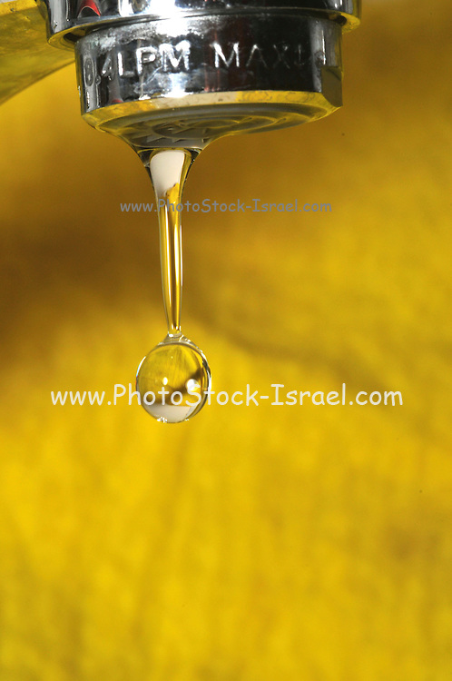 Water dripping from a tap on yellow background