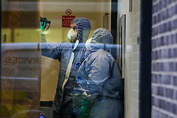 © Licensed to London News Pictures. 23/11/2019. London, UK. Forensic officers look for evidence on the entrance door to Blakeney Tower on Buckle Street in Tower Hamlets, East London following a fatal stabbing.<br /> Police were called to a residential address in Blakeney Tower on Buckle Street, Tower Hamlets in East London at 08.48hrs this morning following reports of a stabbing. A male, in his 20s, was found with stab injuries. Despite the efforts of emergency services, he was pronounced dead at the scene. Three other males with stab injuries were treated at the scene by paramedics before being taken to hospital. Photo credit: Dinendra Haria/LNP