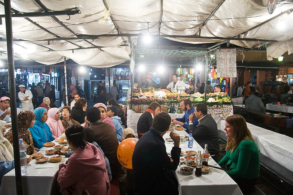 Crowds of tourists sit down to eat dinner at night at one of the many open air eateries in Djemaa El-Fna square in the heart of the Marrakech medina, Morocco. The square bustles with food stalls and performers of all sorts till late every night.
