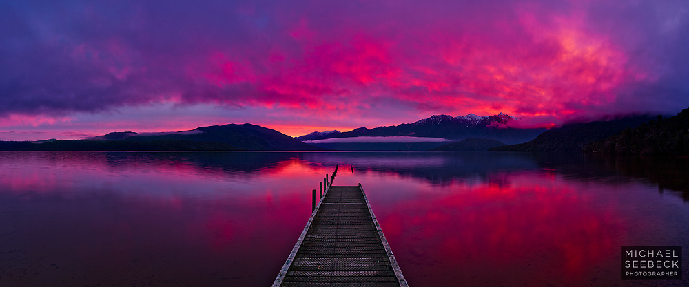 A panoramic photograph of a vivid sunset taken from the shores of a lake in Fiordland, South Island, New Zealand.<br /> <br /> Code: CZSH0001<br /> <br /> Limited Edition Print