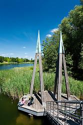 Visitors sitting on wooden footbridge crossing lake at Britzer Garden in Neukolln in Berlin Germany
