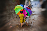 A young boy and young girl holding a colourful umbrella and walking along a street in the rain, Old Varanasi Street, Varanasi, India