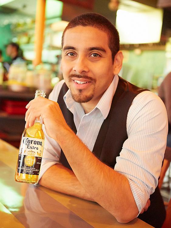 Portrait photograph of Hispanic man drinking Corona Mexican beer