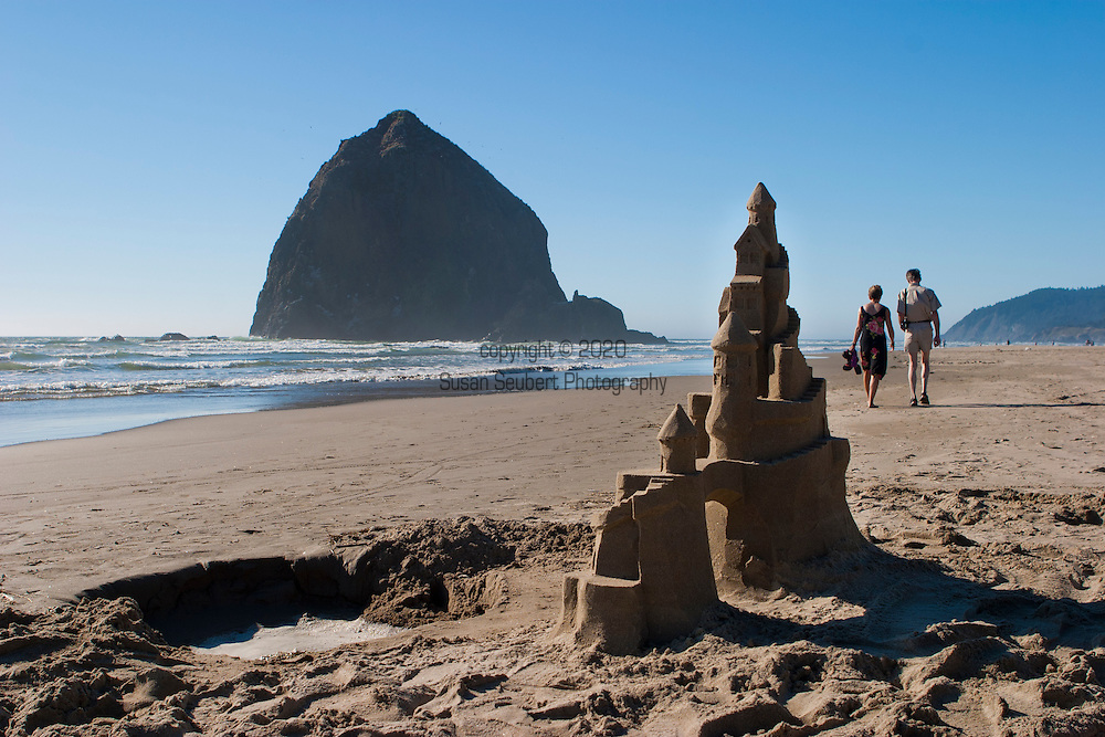 Cannon Beach is recognized by its well-known landmark, Haystack Rock, located to the southwest of downtown Cannon Beach, near Tolovana Park. This igneous rock has an elevation of 235 feet, and is often accessible at low tide, especially in the summertime. There is a small cave system that penetrates the rock and can be seen from the coastline. The rock is also protected as a marine sanctuary, Oregon Islands National Wildlife Refuge, and events are not allowed within 100 feet of either side of the rock.  People strolling by an elaborate sand castle.