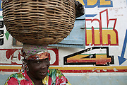 A woman takes a break as she carries a basket filled with small snacks she bought in Carrefour that she is bringing back up the mountain to sell.