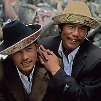 Swarthy young men admire passing girls at a village festival near Lhasa in Tibet.